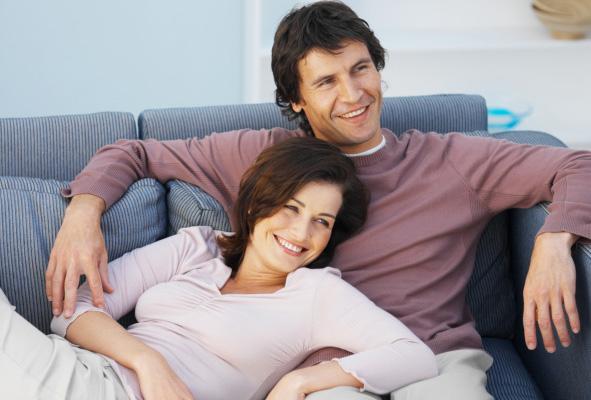 pareja sentados en un sillon ella recostada y él sentado ambos sonriendo