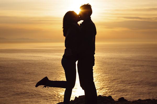 pareja dandose un beso frente al mas en la puesta del sol