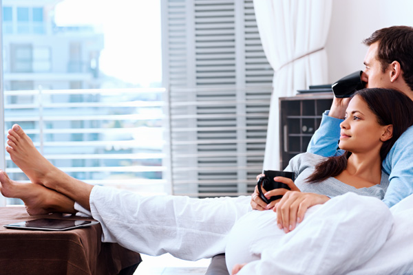 pareja con una taza en la mano, sentados en un sillon entrelazados