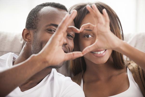 pareja sonriendo, haciendo un corazon con las manos de cada uno