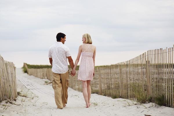 pareja de espaldas camidando tomados de la mano en la playa