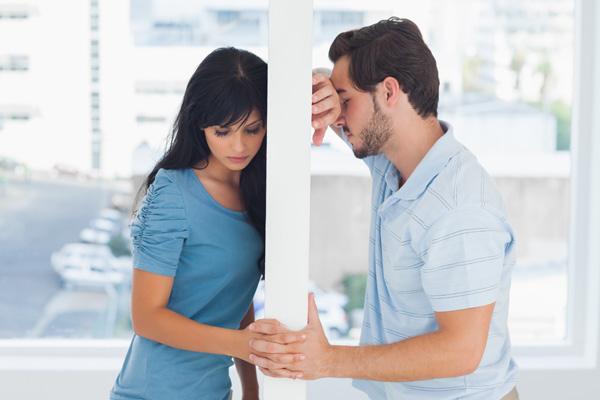 pareja triste con un muro en medio de los dos