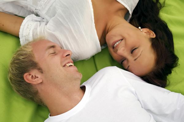 pareja recostastado en la cama con los ojos cerrados y sonriendo