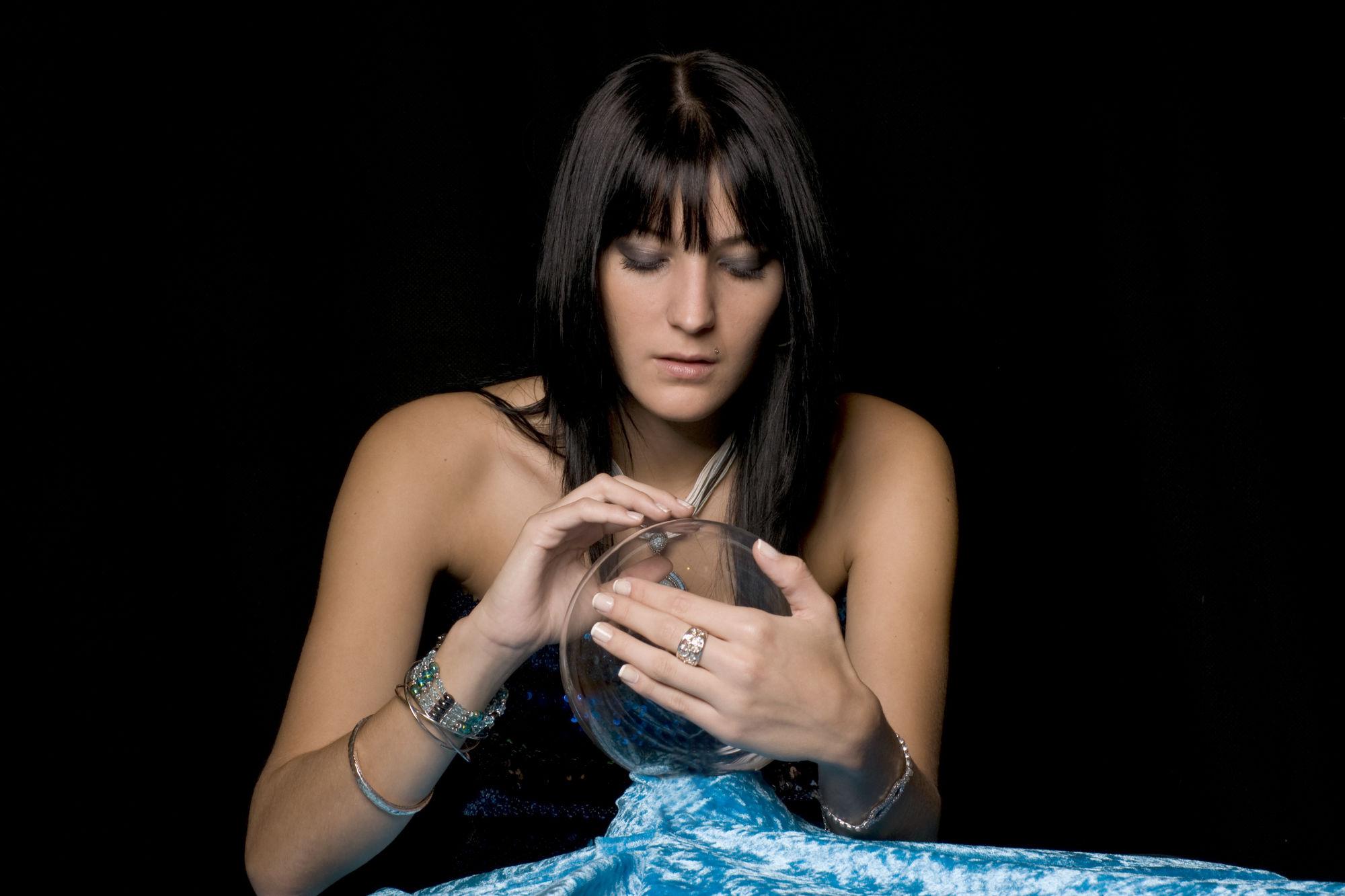 mujer con una bola de cristal entre las manos