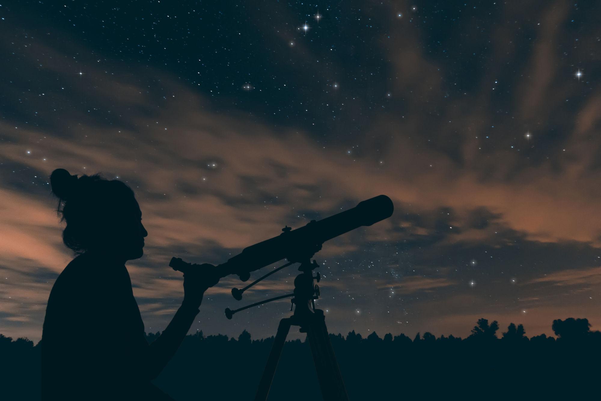 Chica mirando el cielo con telecospio