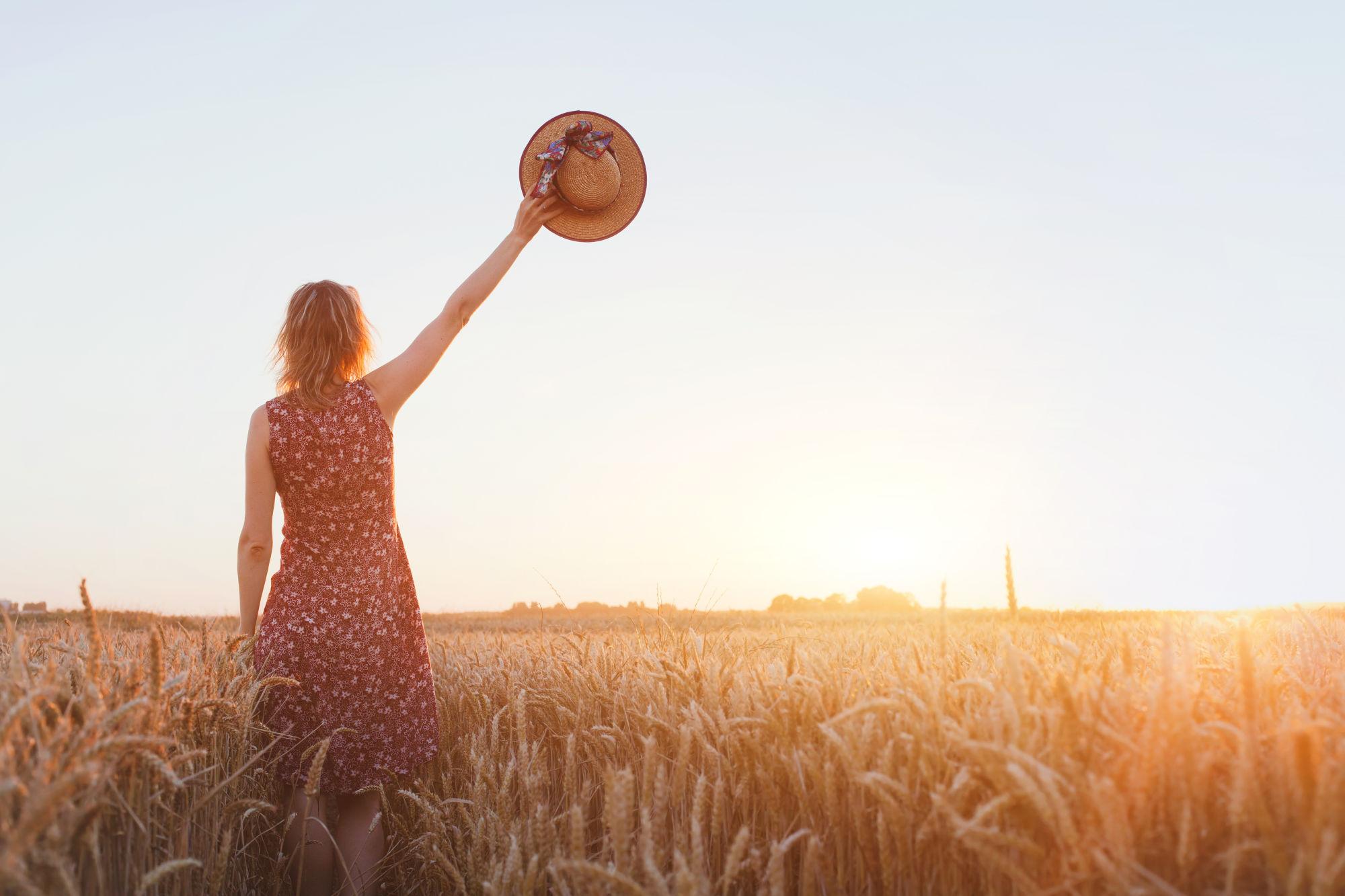 chica en el campo levantando su sombrero