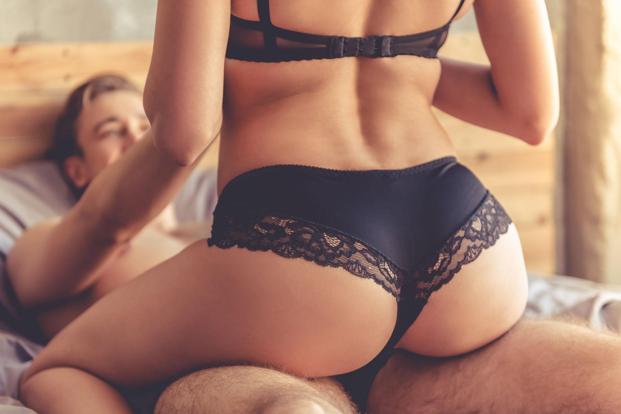 joven encima de su novio en la cama