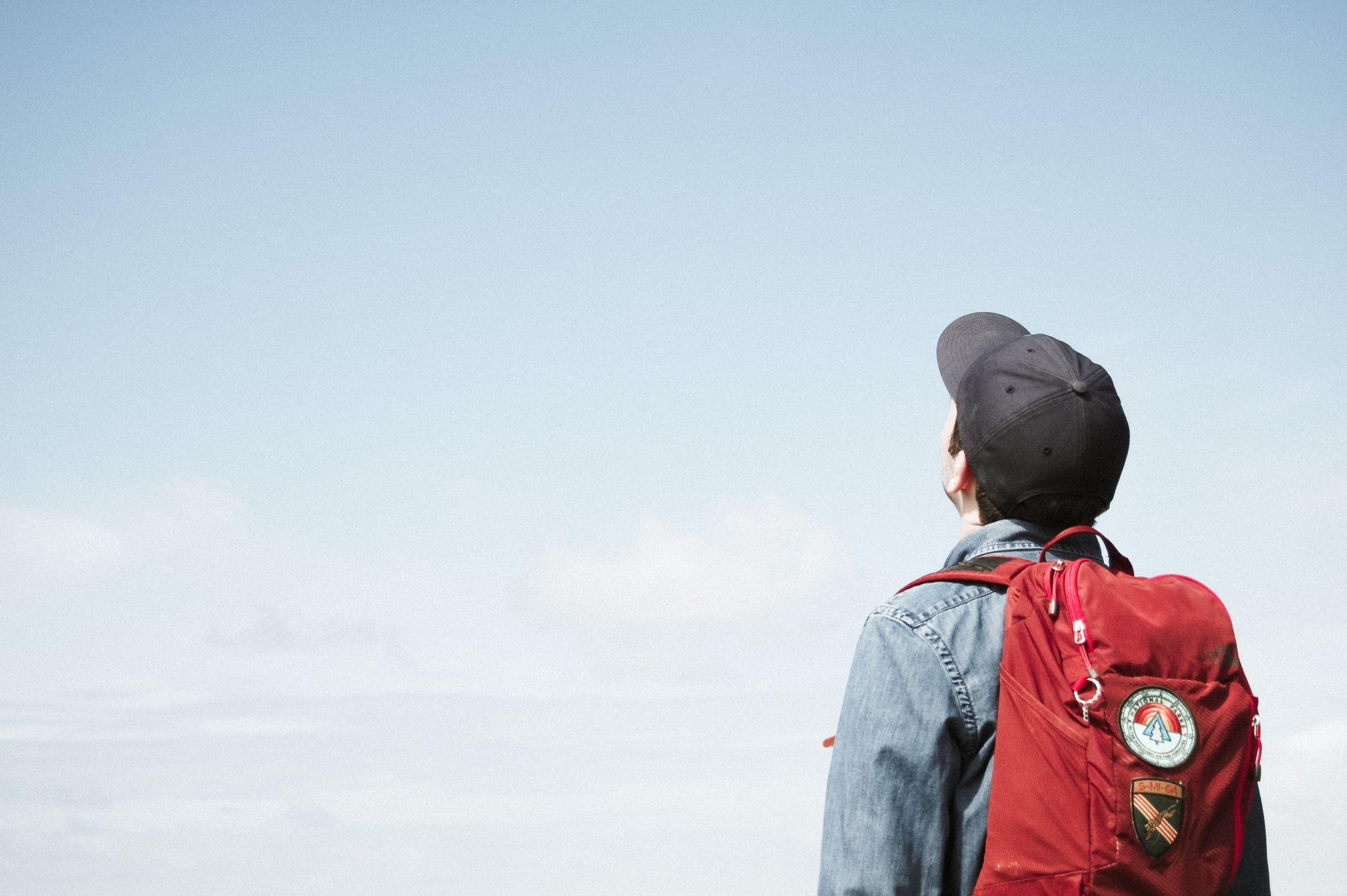 joven con mochila mirando el cielo