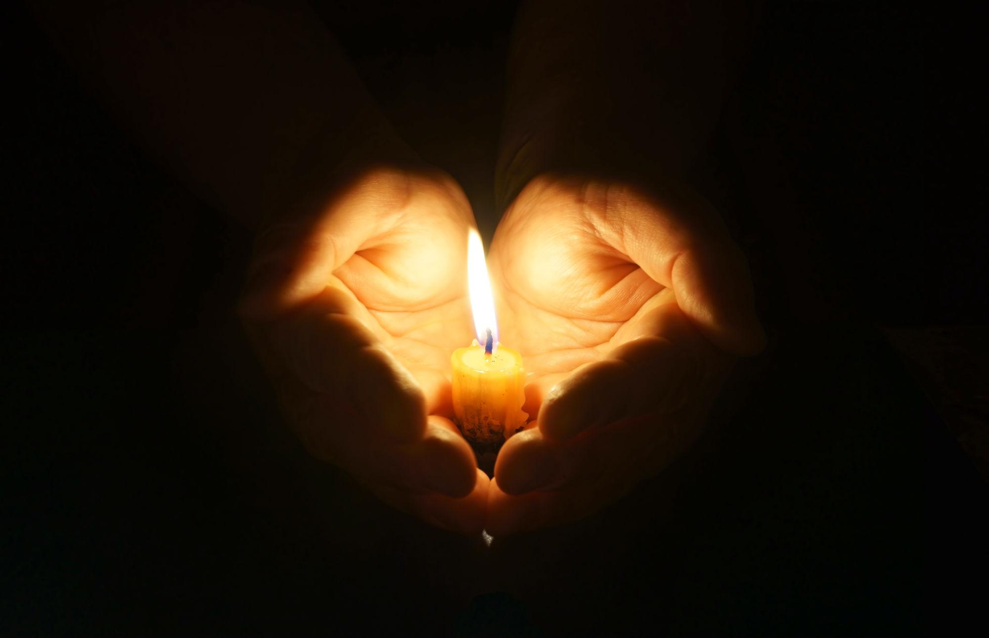 manos con velas en medio