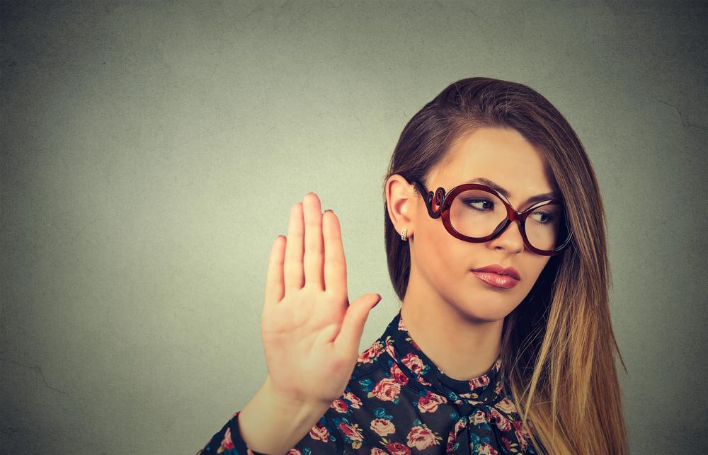 una chica con lentes de pelo largo, haciendo un alto con su mano.