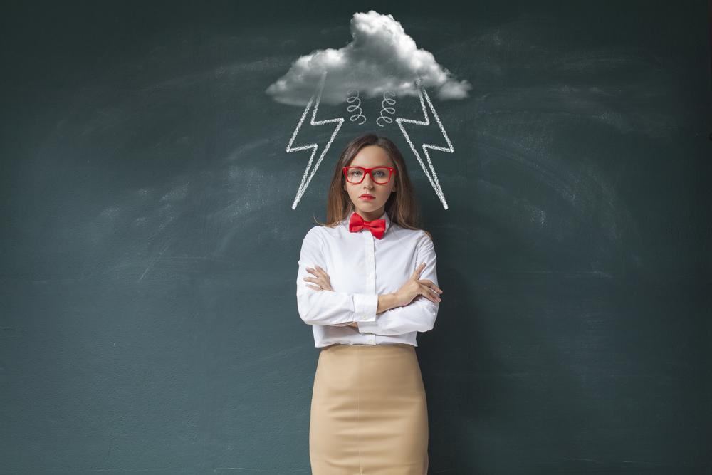 Chica de un aire molesto, delante de una pizarra donde hay una nuve y rayos dibujados sobre su cabeza